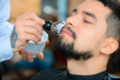 Professional barber shaving the beard of his Royalty Free Stock Photography