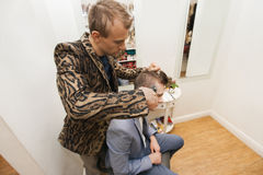 Professional barber shaving male customer's hair in shop Stock Image