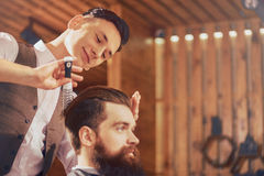 Professional barber styling hair of the client. Like what you do. Positive delighted skillful barber holding hair brush and expressing gladness while styling stock image