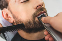 Professional barber using electric machine for haircut Stock Photo