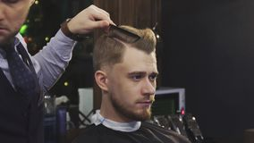 Professional barber using hairspray and blow dryer styling hair of a client. Close up of a handsome young man getting his hair styled by a professional barber stock video