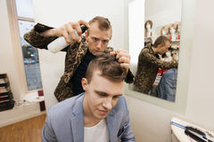 Professional barber using hairspray on male customer in shop Royalty Free Stock Image