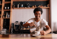 Professional barista making coffee. On counter at cafe. Young african man pouring milk into cop and smiling Stock Photo