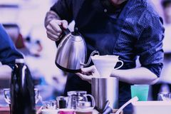 Professional barista pouring boiling water from special kettle into filter, preparation of filter coffee. Purple color royalty free stock images