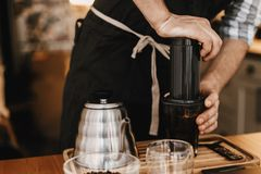 Professional barista preparing coffee in aeropress, alternative coffee brewing method. Hands on aeropress and glass cup, scales,. Manual grinder, coffee beans stock photos