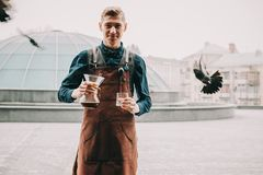 Professional barista preparing coffee alternative method. Outdoors Barista pours coffee into a glass Stock Image