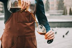Professional barista preparing coffee alternative method. Outdoors Barista pours coffee into a glass Stock Photo
