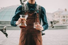 Professional barista preparing coffee alternative method. Outdoors Barista pours coffee into a glass Royalty Free Stock Photos
