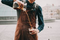 Professional barista preparing coffee alternative method. Outdoors Barista pours coffee into a glass Royalty Free Stock Photography
