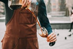 Professional barista preparing coffee alternative method. Outdoors Barista pours coffee into a glass Stock Photos