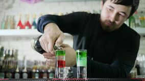 Professional barkeeper makes bright beverage and slowly pouring vivid liquor from bottle into glass with alcohol in bar. Professional barkeeper makes bright stock video footage