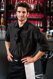 Professional barman in black standing bar. Portrait of handsome barman standing in front of the bar Royalty Free Stock Photo