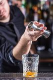 Professional barman making alcoholic cocktail drink old fashioned.  royalty free stock photography