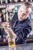 Professional barman making alcoholic cocktail drink old fashioned.  stock photography