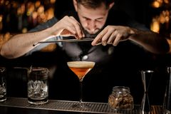 Professional bartender adding to a cocktail in the glass with a whipped cream a grated nutmeg stock photo