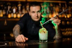 Professional bartender adding to a glass with dried orange and ice a smoked cinnamon with tweezers. Professional bartender adding to the glass with a dried stock photography