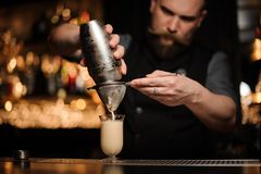 Professional bartender with a beard pouring cocktail from the steel shaker through the sieve royalty free stock photography
