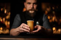 Professional bartender with a beard serving a cocktail in the glass with foam decorated with a one red rose bud royalty free stock photo