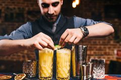 Professional barman garnishing with lime cocktails stock images