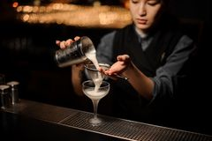 Professional bartender girl pouring a delicious cocktail from the steel shaker through the sieve. To a glass on the bar counter on the blurred background royalty free stock image
