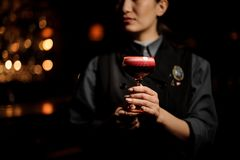Professional bartender girl serving a smooth crimson cocktail in the glass with a one pink rose bud as a decor stock photography