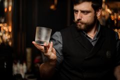 Professional bartender holding in hand a cold matte cocktail glass royalty free stock image