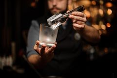 Professional bartender holding in hand an ice cube in tweezers putting it on the a cold matte cocktail glass stock image