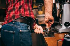 Professional bartender making coffee and preparing tamper with fresh roasted coffee in cafe bar, pub or restaurant Stock Photo