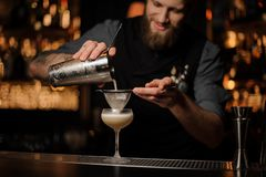Professional bartender pouring a delicious cocktail from the steel shaker through the sieve. To a glass on the bar counter on the blurred background royalty free stock photos