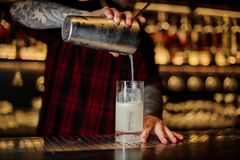 Professional bartender pouring a Gin Fizz cocktail from the steel shaker. To a glass on the bar counter stock images