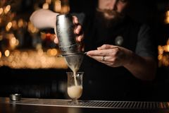 Professional bartender pouring cocktail from the shaker through the sieve. Professional bartender pouring from the shaker through the sieve to a glass on the bar royalty free stock photography