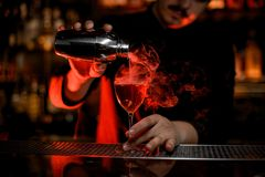 Professional bartender pouring a smoke into the cocktail glass from the steel shaker royalty free stock images