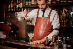 Professional bartender pourring cocktail with an ice cubes into stock image