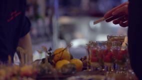 Professional bartender preparing a cocktail with ice a mix of alcohol. The barman measure quantities for a perfect. Cocktail and mixes all together stock footage