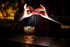 Professional bartender in red shirt adding orange zest juice to a Rusty Nail cocktail stock photo