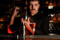 Professional bartender spraying from the diffuser on the cocktail in the glass stock images