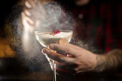 Professional bartender spraying with flavor on a Twinkle cocktail in the bar royalty free stock image