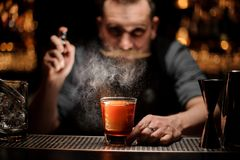 Professional bartender spraying to the cocktail glass with one big ice cube under the light stock images