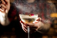 Professional bartender spraying on the Twinkle cocktail in the bar royalty free stock image