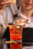 Professional bartender throwing to red cocktail glass stock photo
