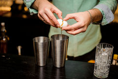 Professional bartender at work in bar pouring egg yolk into glass for drink. Barman`s hands in bar interior making alcohol cocktail. Professional bartender at stock photography