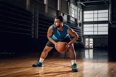 Professional basketball player in an action in basketball field. Full body portrait of Black professional basketball player in an action in basketball field Royalty Free Stock Photo