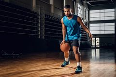 Professional basketball player in an action in basketball field. Full body portrait of Black professional basketball player in an action in basketball field Stock Photos