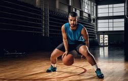 Professional basketball player in an action in basketball field. Full body portrait of Black professional basketball player in an action in basketball field Stock Photo