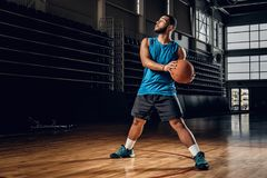 Professional basketball player in an action in basketball field. Full body portrait of Black professional basketball player in an action in basketball field Royalty Free Stock Image