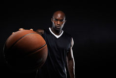 Professional basketball player against black background Royalty Free Stock Image
