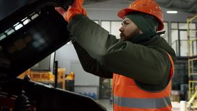 Professional bearded car mechanic screwing details of car with special tool on lifted automobile at repair service stock footage
