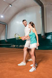 Professional bearded instructor teaching young woman to play tennis Royalty Free Stock Image