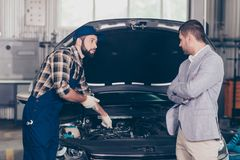 Professional bearded mechanic in safety blue overall, checkered royalty free stock photos
