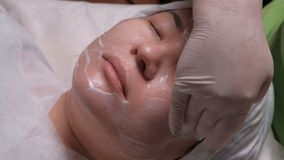 A professional beautician applies a nourishing cream on the face of an Asian girl. Women`s skin rejuvenation procedure in a beauty. Close-up. A professional stock video footage